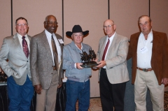 Bill Morrison receives the Breeder of the Year award from Larry Parker and other Brangus friends